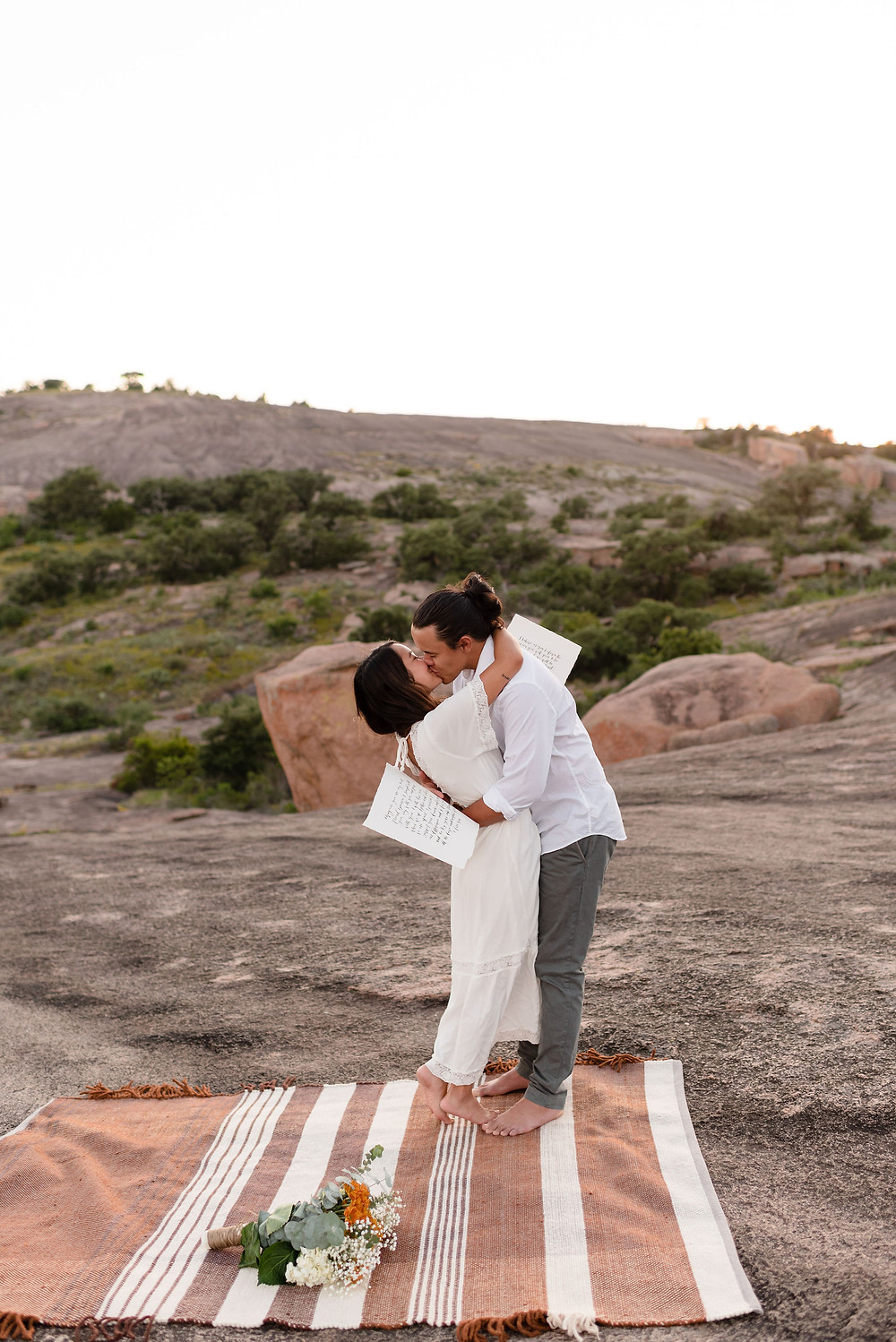 couple's first kiss after elopement ceremony at enchanted rock. groom has bride in a slight backbend