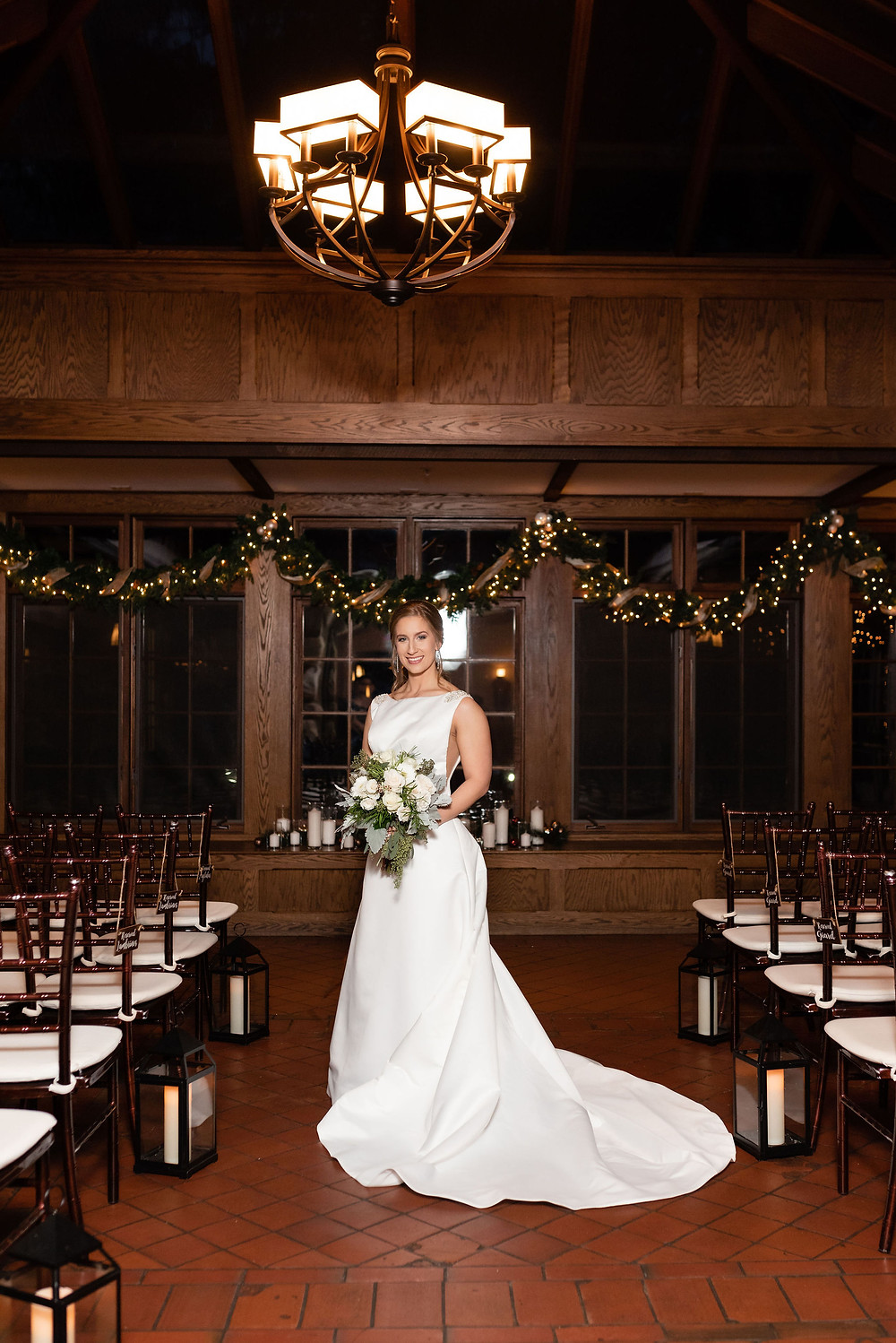 bridal portrait in the ceremony room at willowdale estate. candles lit and twinkle lights around garland for the christmas themed wedding