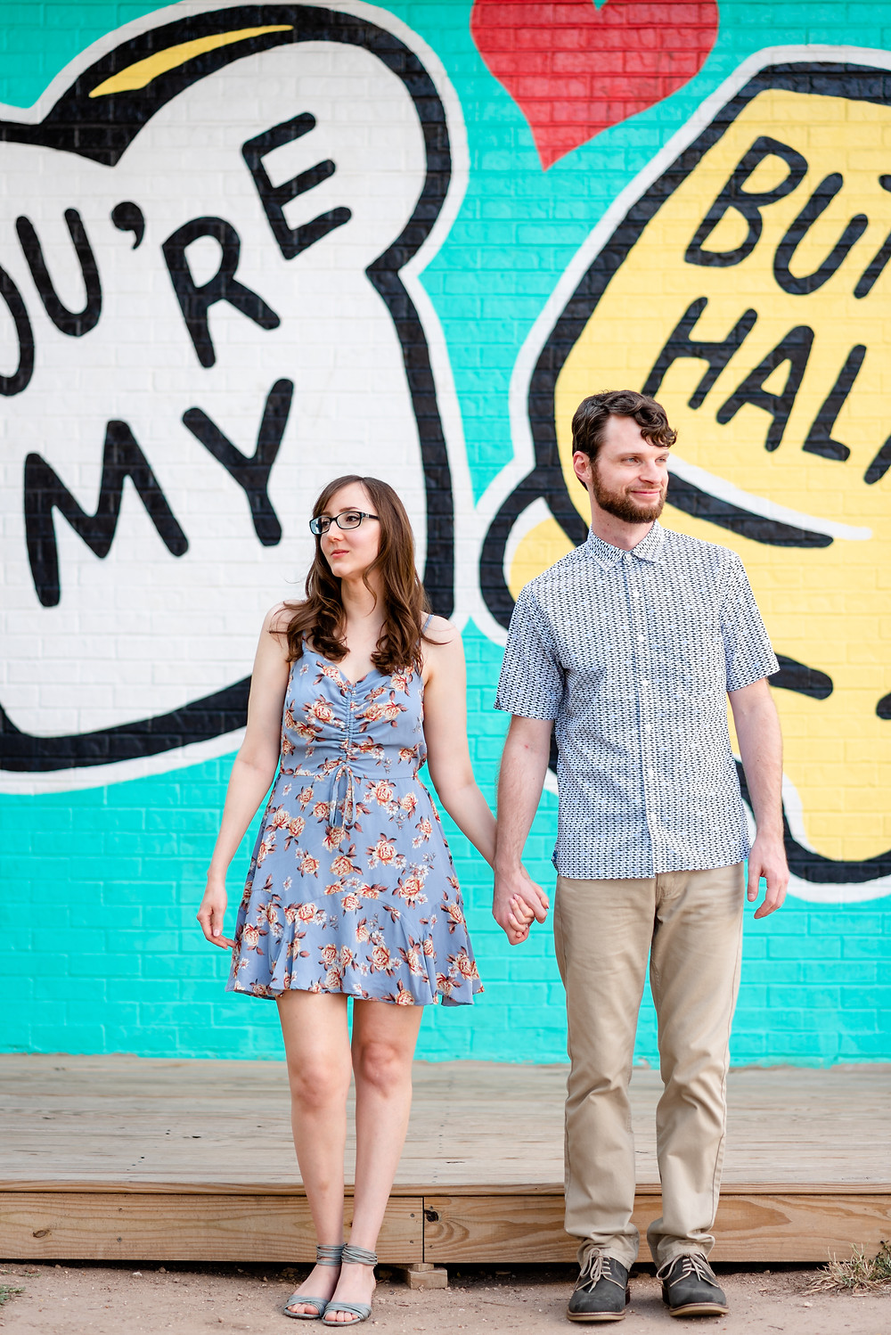 "Guy and girl stand side by side holding hands. They are looking in opposite directions. They're standing in front of the ""you're my butter half"" mural in austin for their engagement photos"