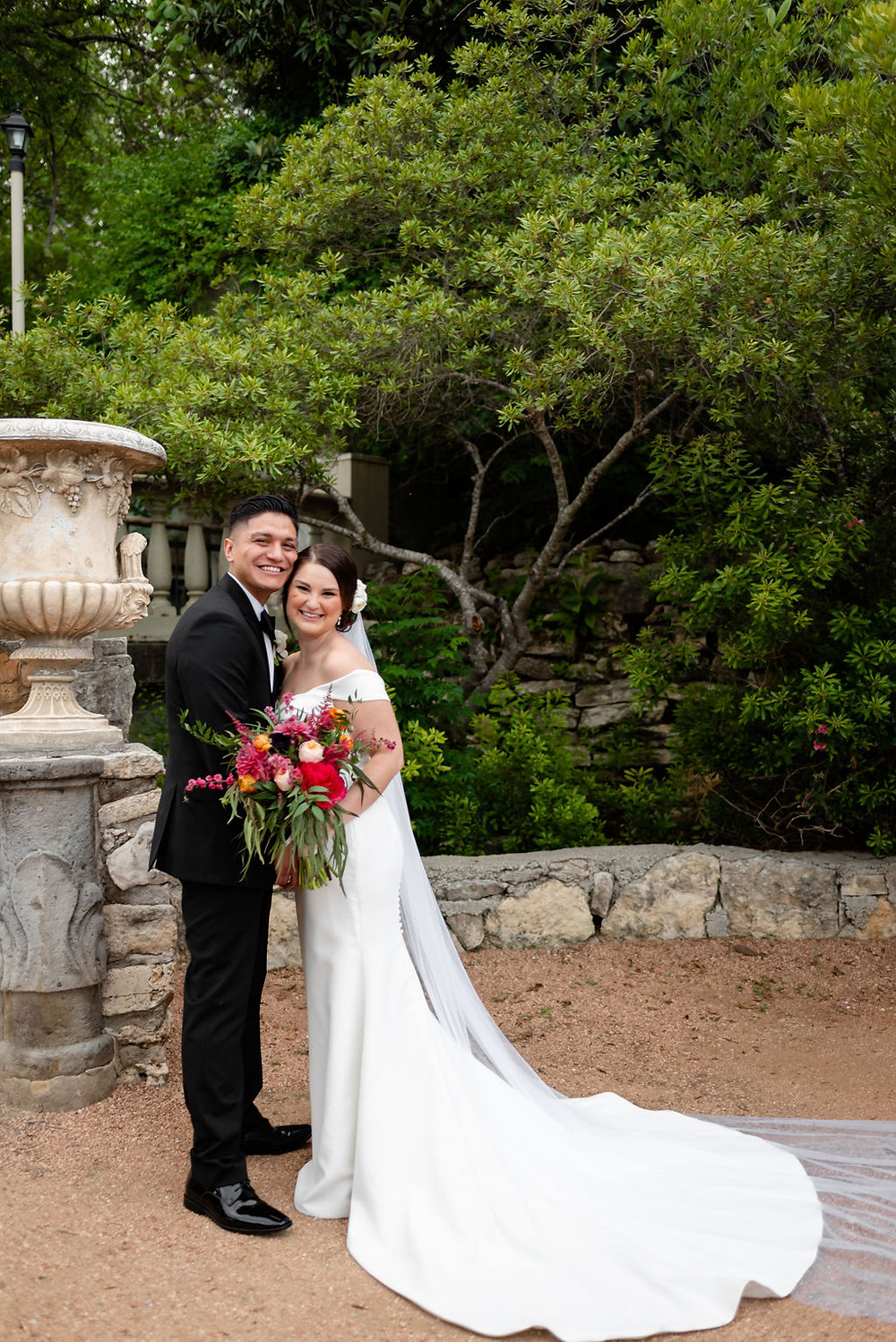 bride and groom pose in butterfly garden at villa antonia