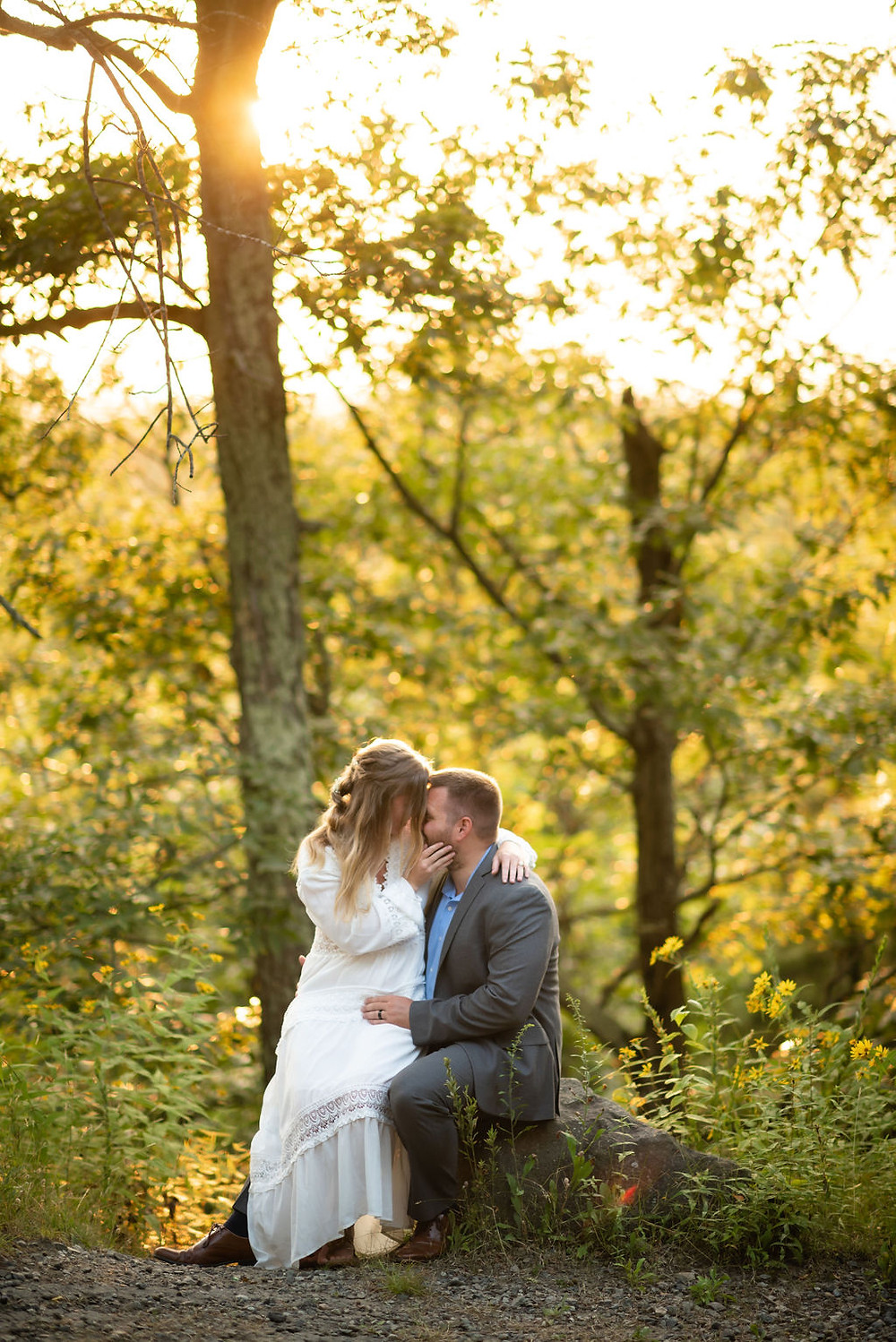 groom sits on rock, bride sits on his leg. they are forehead to forehead and the brides hand is on the groom's face. the sun is setting behind them through the trees with beautiful golden hour light
