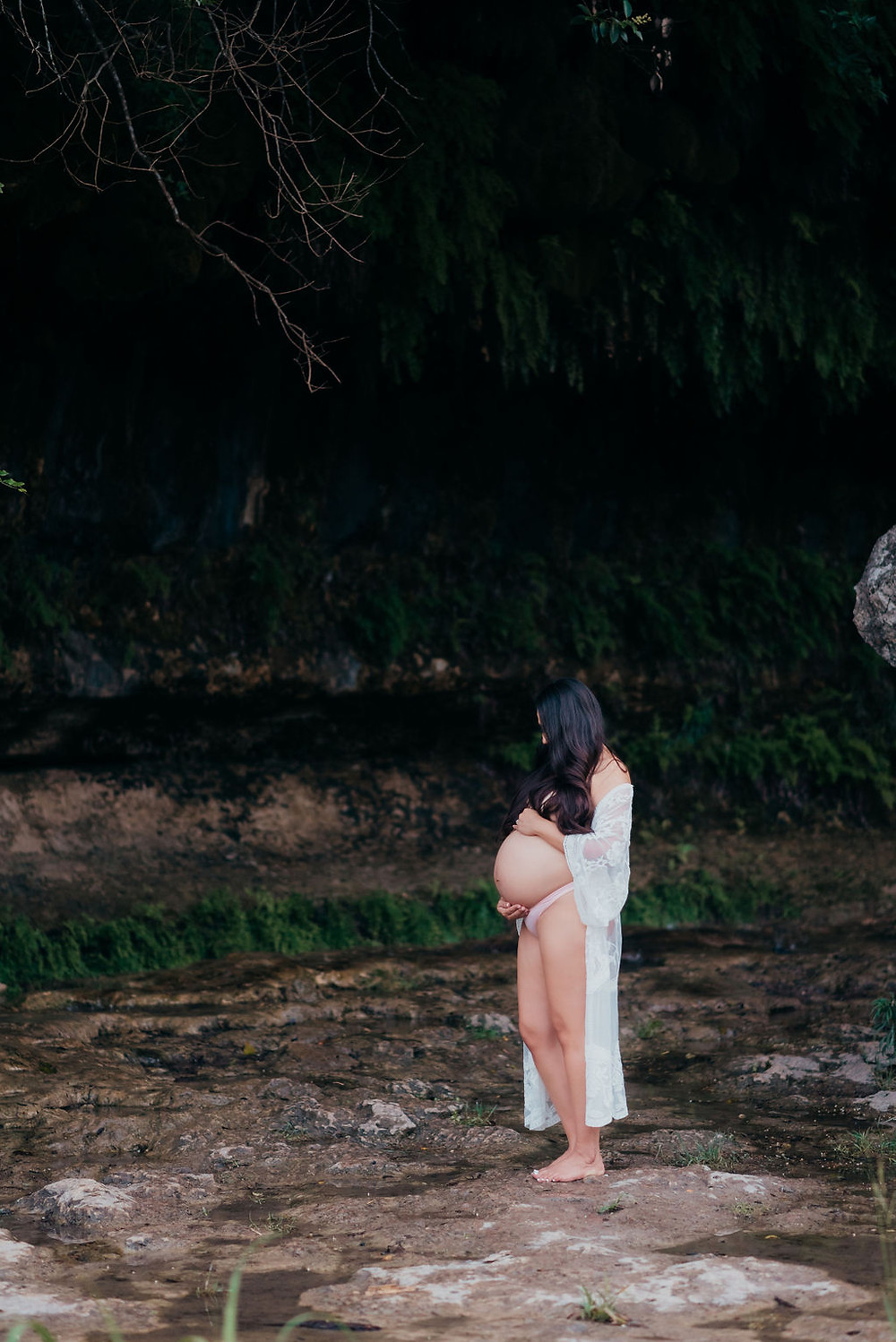 pregnant woman looks down at her baby belly. her hair shrouds her face to give an element of mystery. she is wearing a white lacy coverup that is open in front to show off her bare pregnant belly