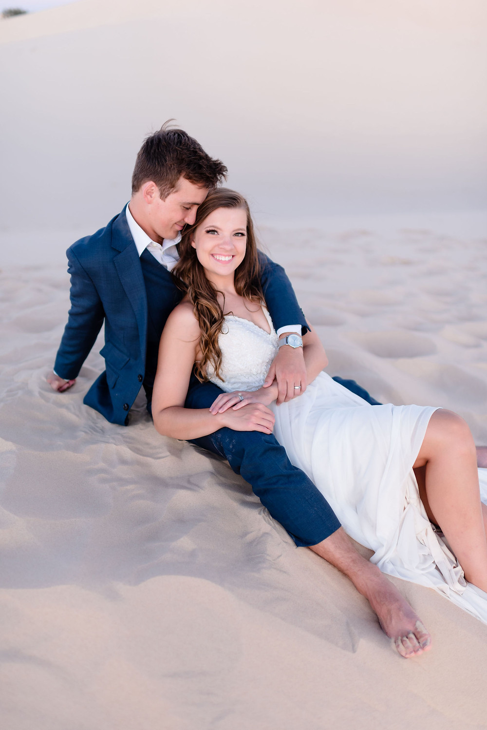 girl sits in between guy's legs. guy's face is down, facing the side of her head. she is smiling at the camera.