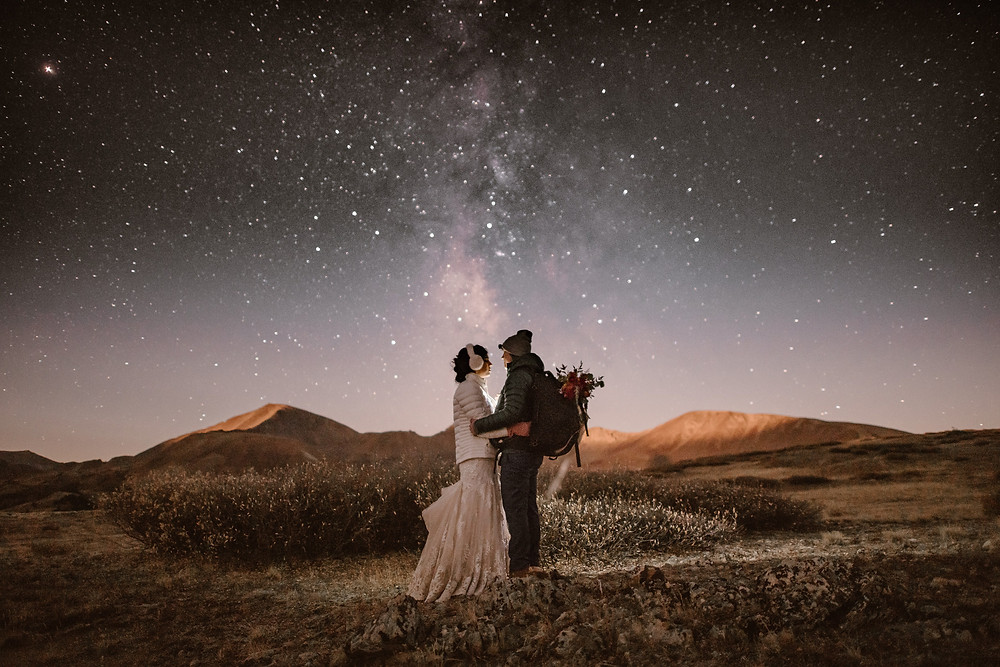 couple standing in a field at night with the milky way in the sky behind them. Illuminated by OCF behind them