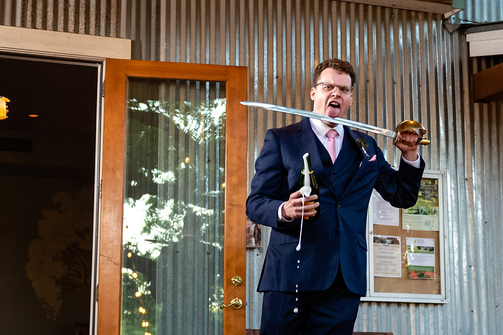 best man licking a sword after sabring a bottle of champagne