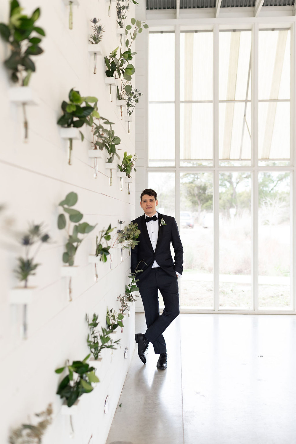 groom portrait leaning against white wall covered in plants