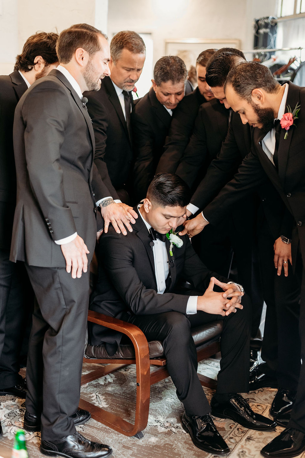 groomsmen praying over groom before wedding at villa antonia