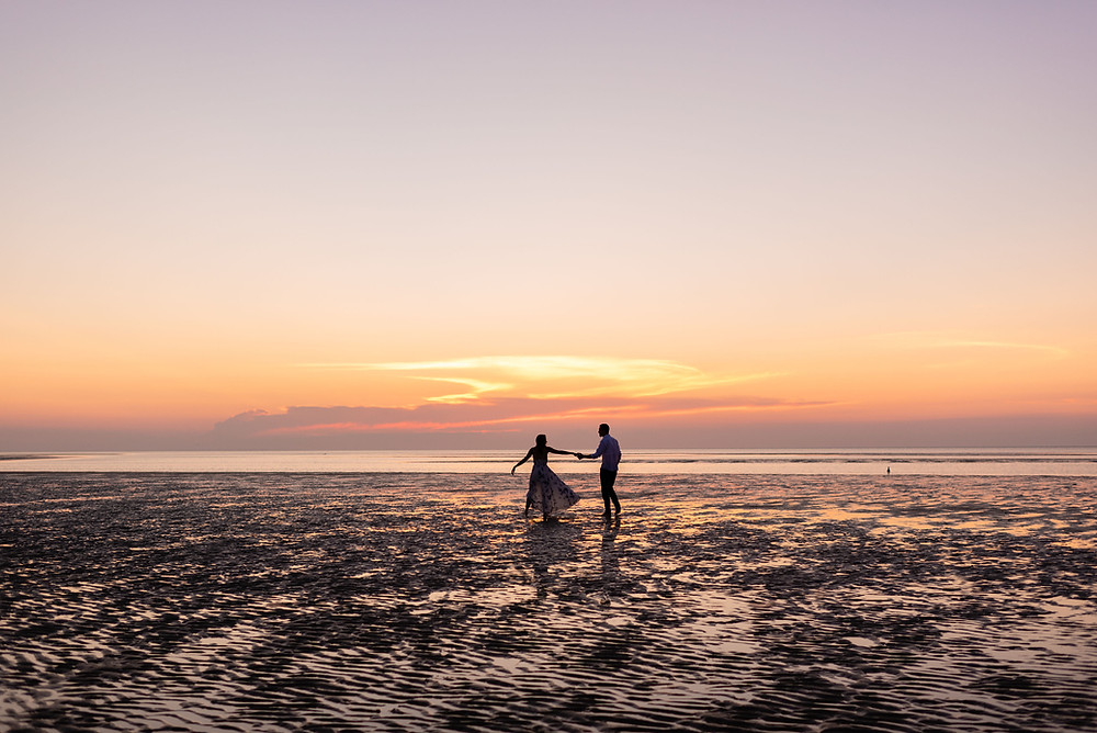couple dances on a sandbar during low tide on Brewster beach during sunset