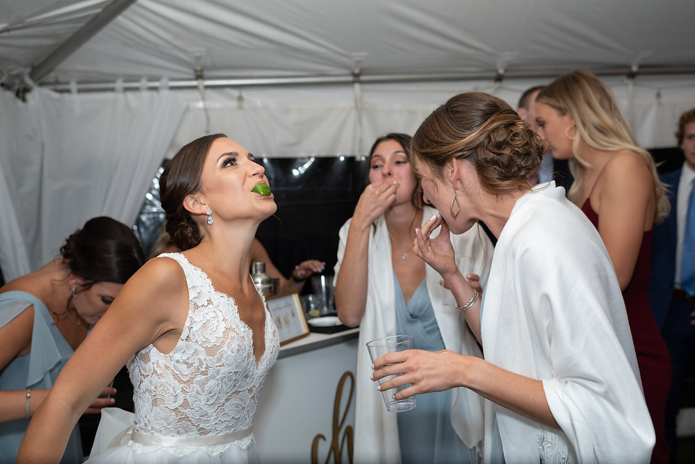 silly photo of bride with friends taking tequila shots and sucking on a lime