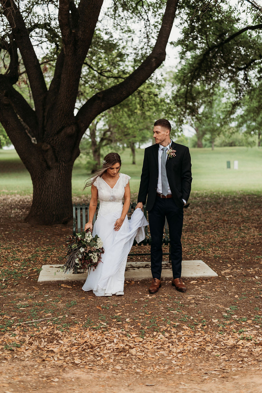 bride and groom stand side by side looking in opposite ways. they are standing in front of a bench at festival beach near lady bird lake during their Austin elopement