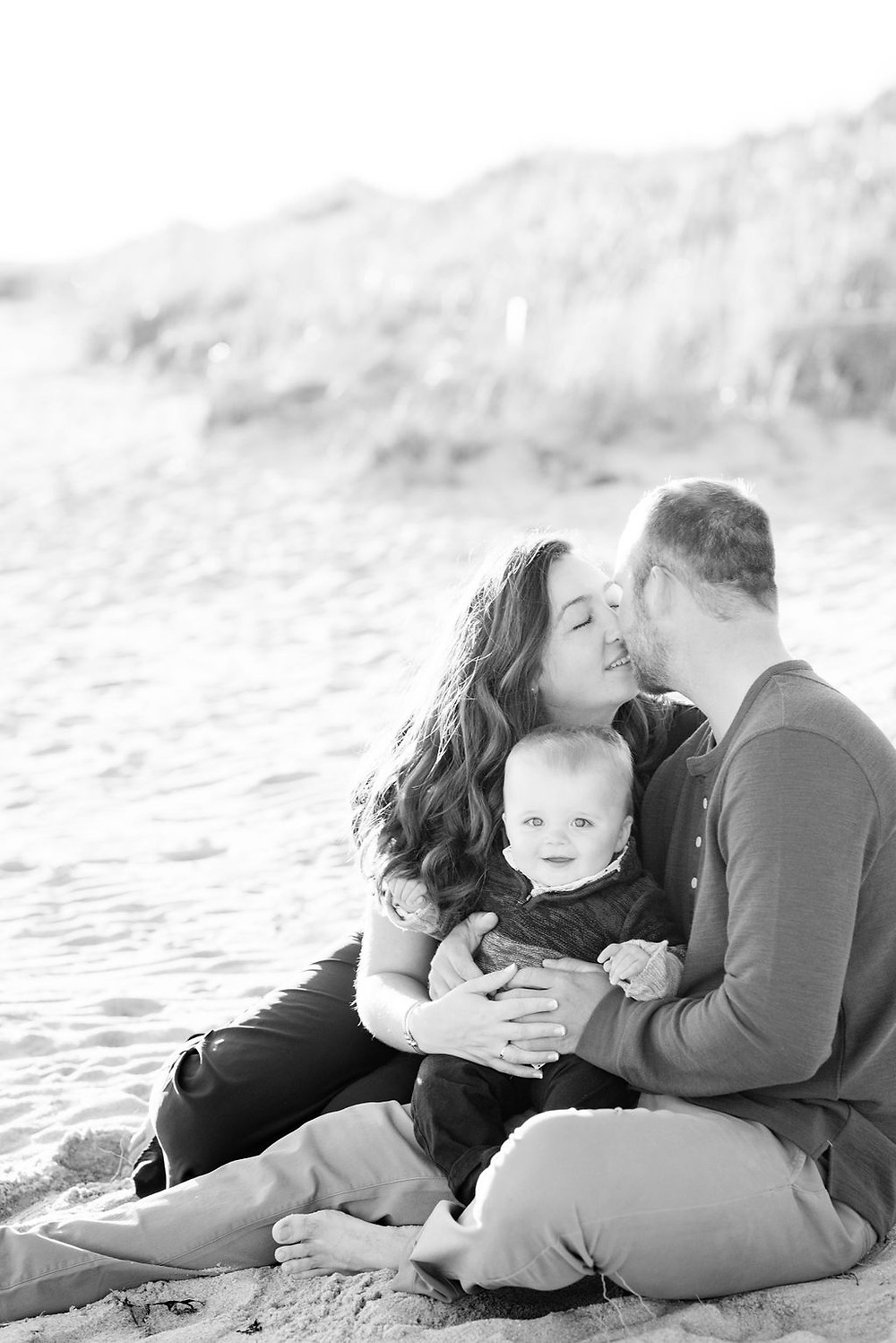 couple sitting on beach with son for engagement photos at lighthouse inn in West Dennis Cape cod, MA