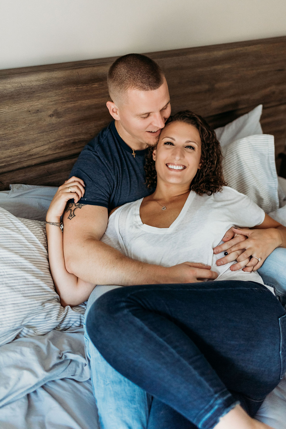 in home engagement session with couple posed laying on bed