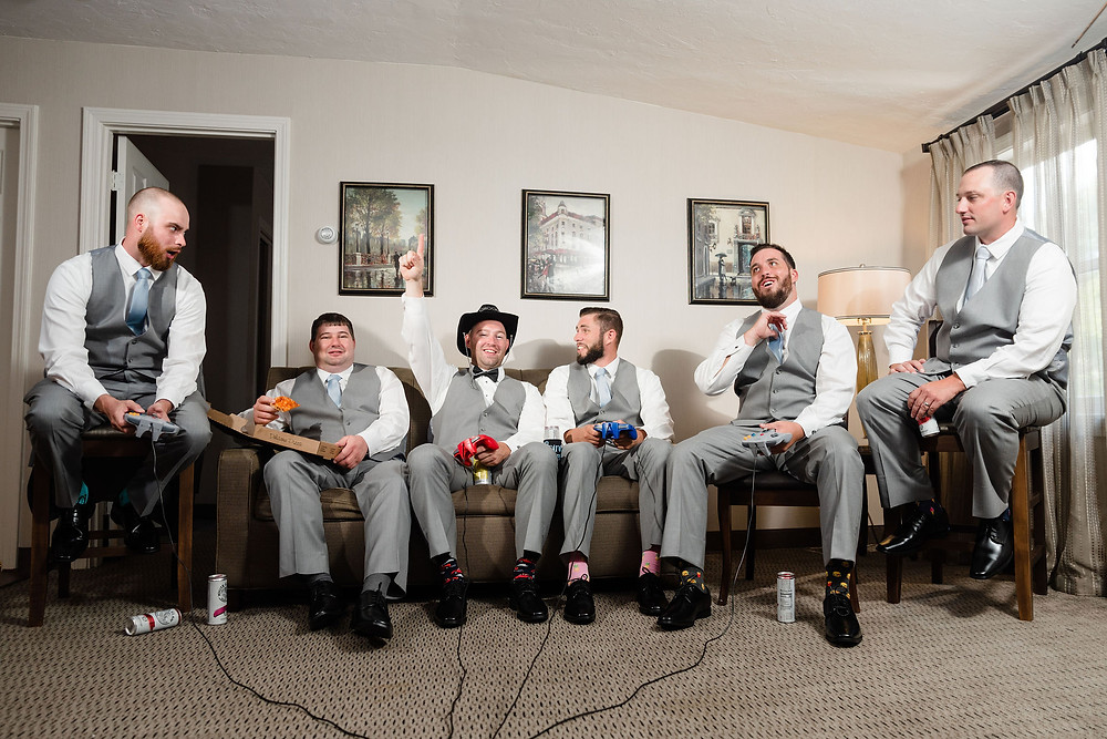 groomsmen hanging out in hotel room playing video games and drinking