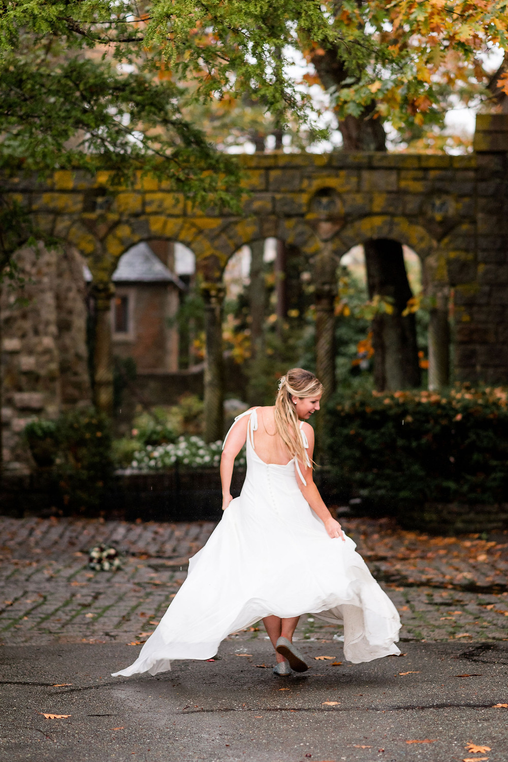 bride twirls in her wedding dress. fall foliage and castle architecture in background
