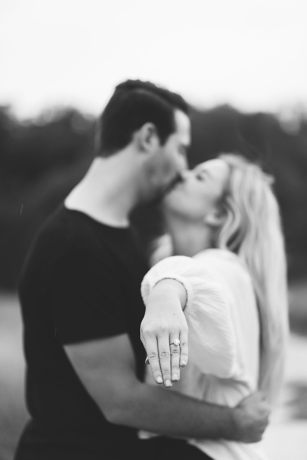 girl has her hand extended towards the camera to show off her new engagement ring, couple kisses in the background out of focus