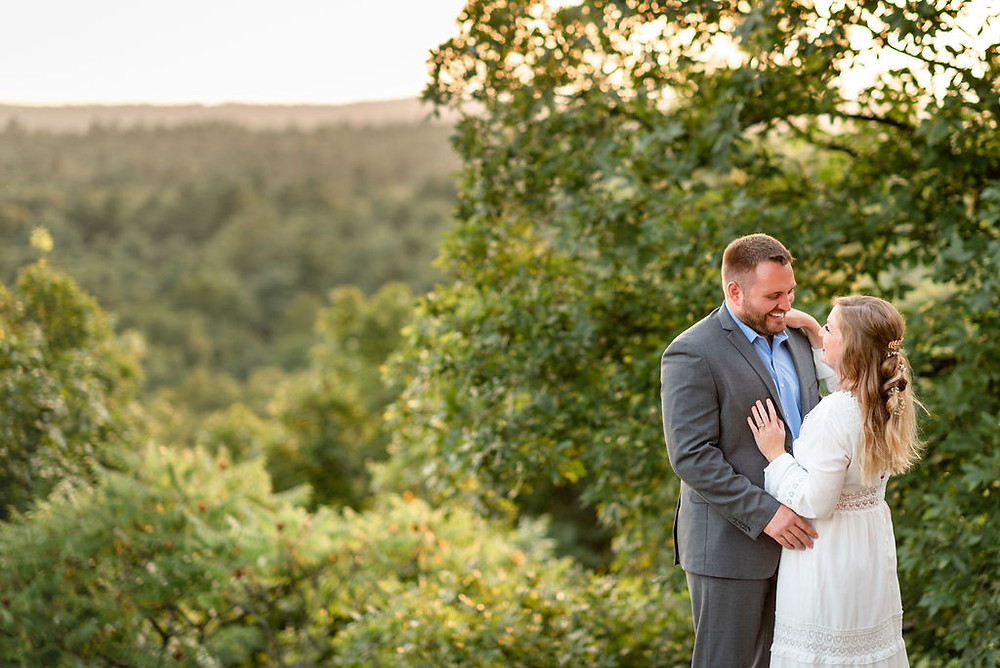 bride and groom stand chest to chest smiling at each other. they are to the right side of the frame, with a beautiful expansive view of trees in the distance which is on middlesex fells reservation