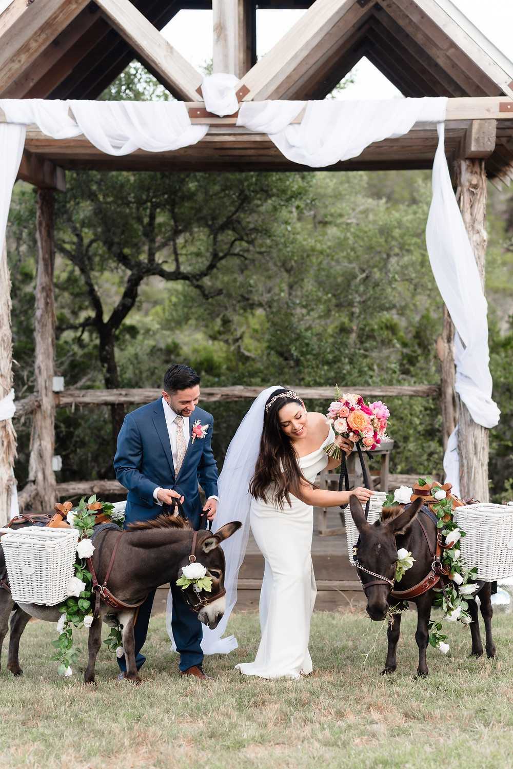 the wedding couple pets donkeys, which don flowers and baskets filled with beer. they are called beer burros and they came from the company Ears With Beers