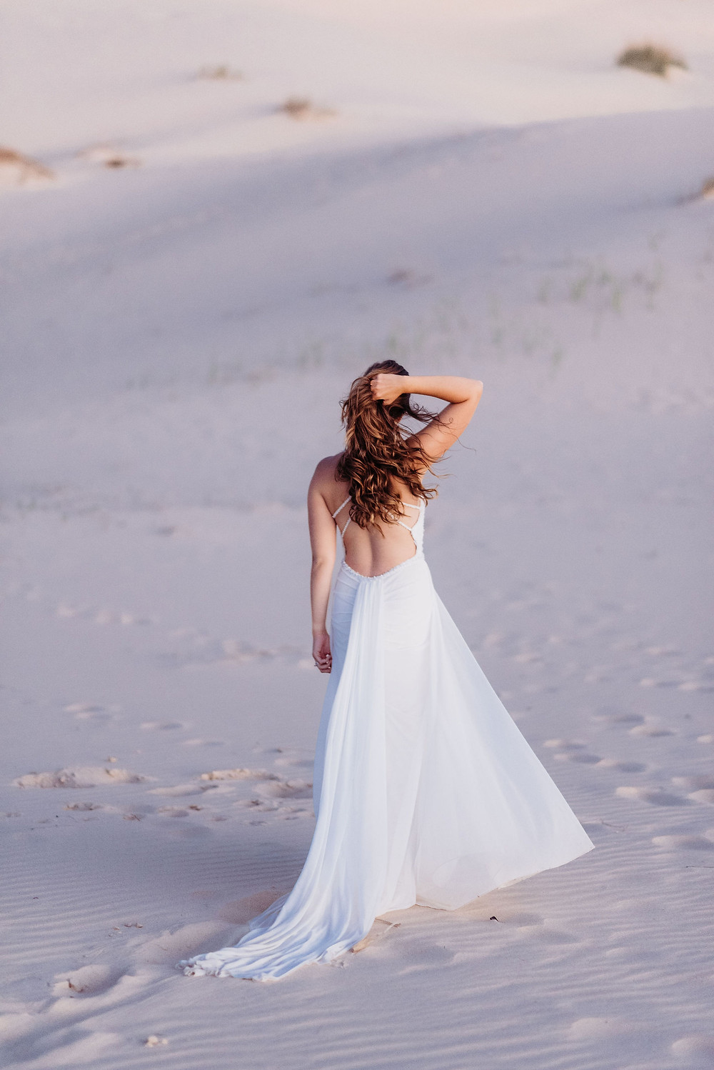 bride is alone facing away from the camera. she is holding her curly hair to keep it from blowing around from the wind. he dress is blowing in the wind