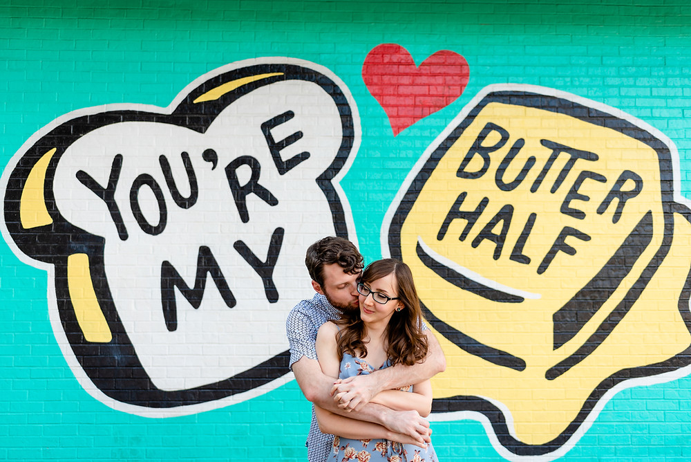 "guy is standing behind girl with his arms wrapped around her and kissing her cheek. They're standing in front of the ""you're my butter half"" mural in austin for their engagement photos"