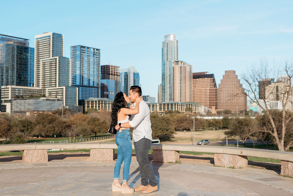 doug sahm hill downtown austin proposal. couple kisses after getting engaged with the Austin skyline in the background