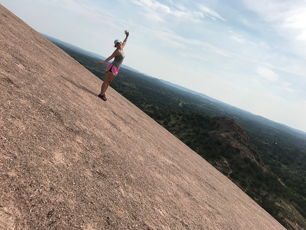 hiker standing on pink granite surface of enchanted rock