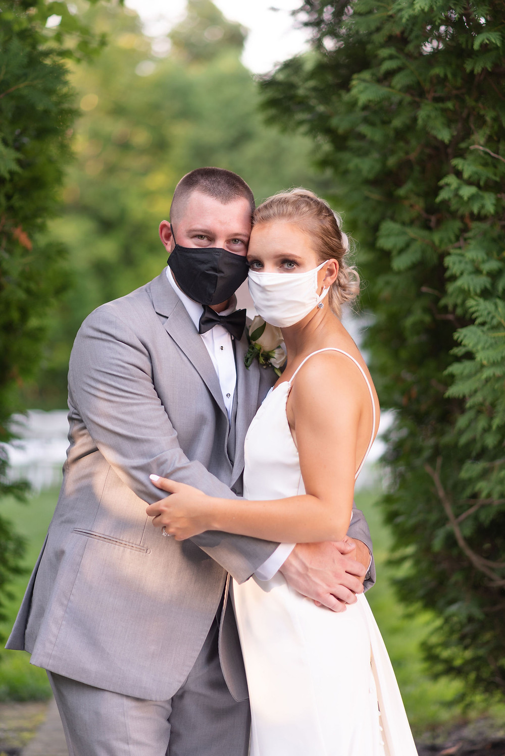 bride and groom pose in masks during COIVD-19 wedding