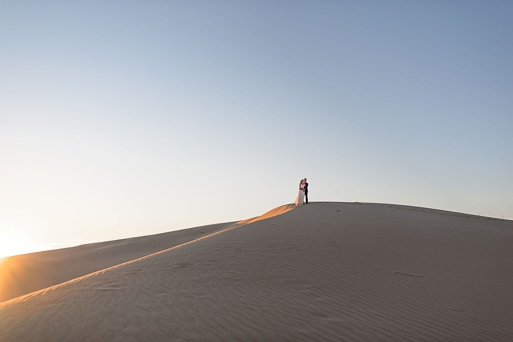 wide angle view from the base of a sand hill. the couple stands on the top of the hill with the sky as the backdrop. the sun sets in the lower left of the frame. the left side of the hill is slightly illuminated by the sun which creates a golden leading line all the way from the side of the frame to the couple