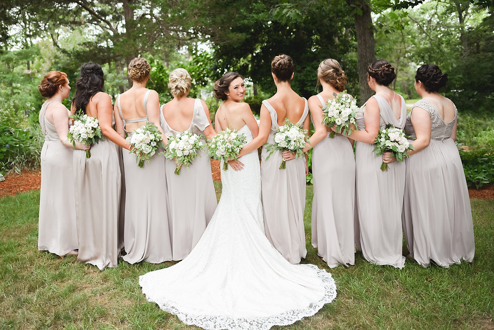back of bridesmaids dresses with bride turned around smiling at camera