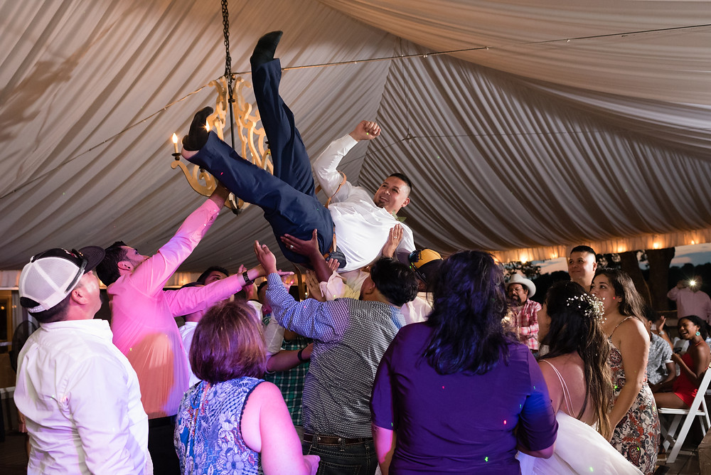 groom being thrown in the air at wedding reception