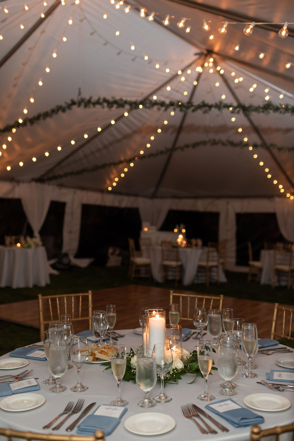 wedding reception table details under tent with twinkle lights