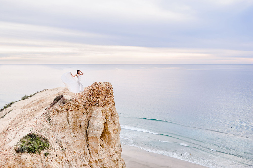 bride standing on cliff at ho chi minh trail with sunset skies