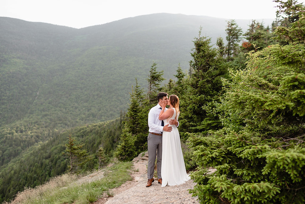 bride and groom kissing with trees surrounding them and mountains in the background