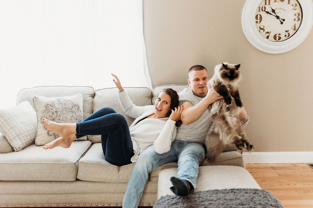 in home engagement session candid photo of couple on couch with cat