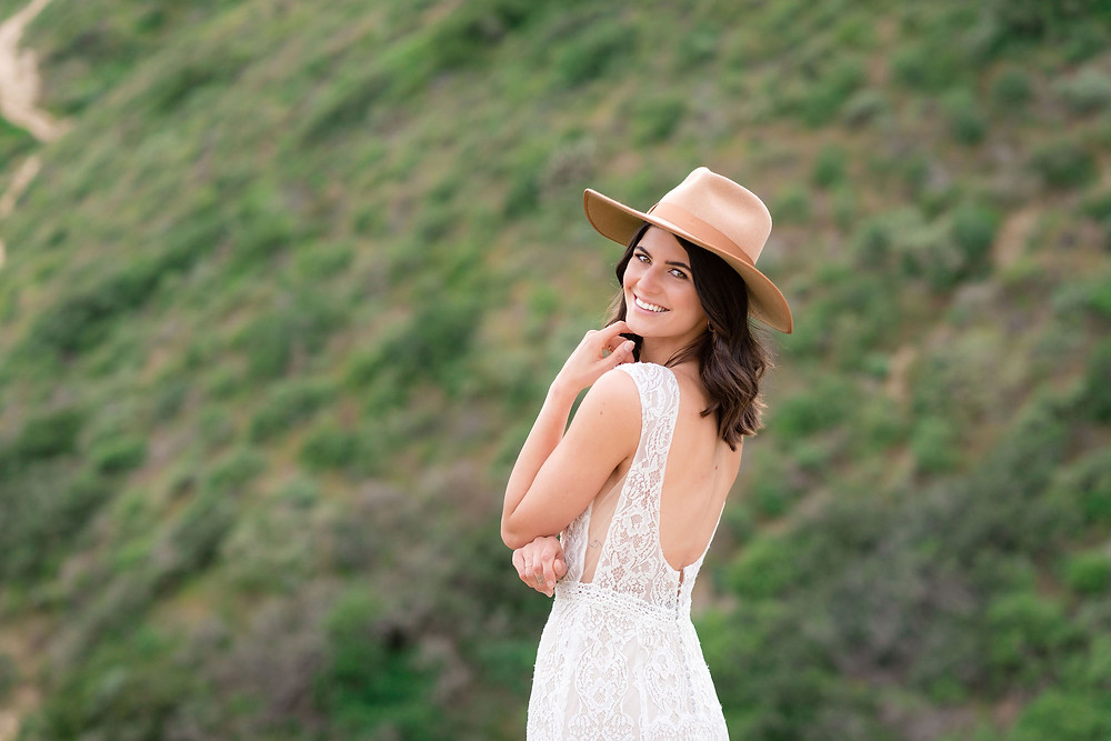 bride looking over her shoulder at camera wearing a stylish hat with wedding dress