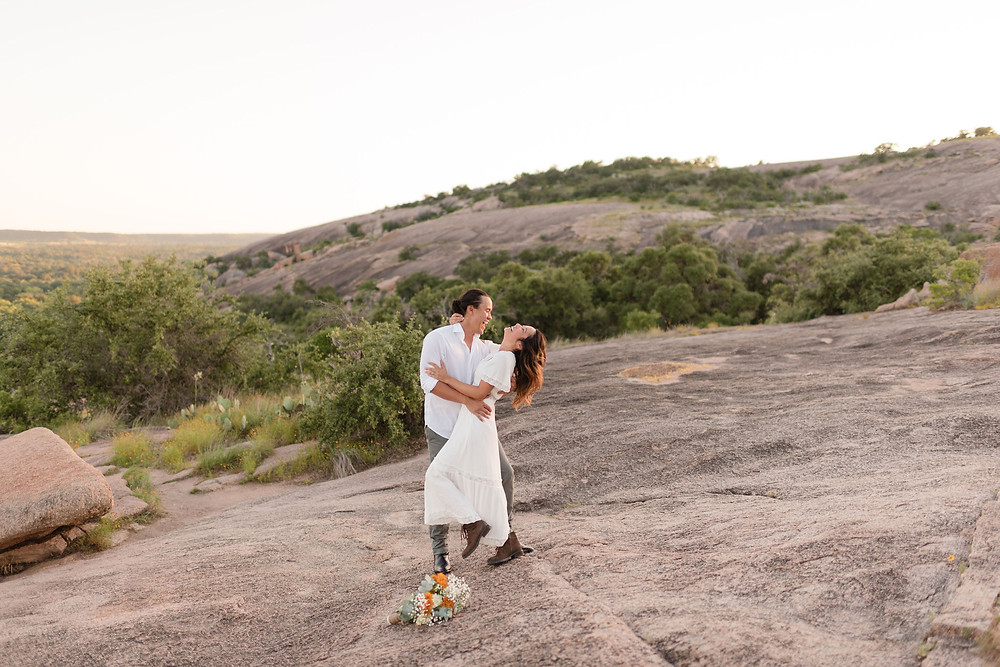 bride and groom laughing together on a mountainside