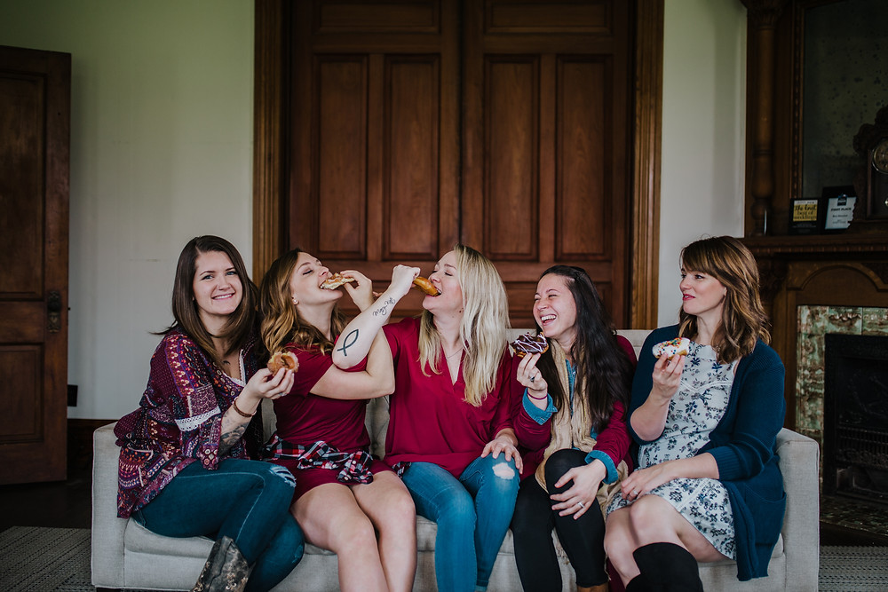 girls eating donuts sitting on a couch