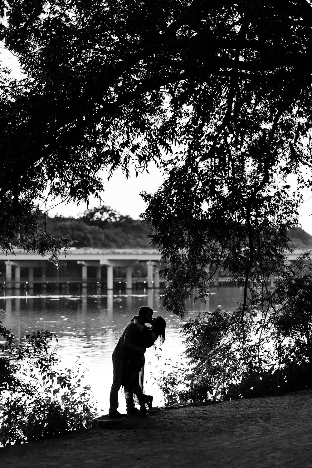 girl and guy embrace in a kiss next to lady bird lake in austin. it is a black and white silhouette photo. you can see the couple, trees, lady bird lake, and the congress street bridge.