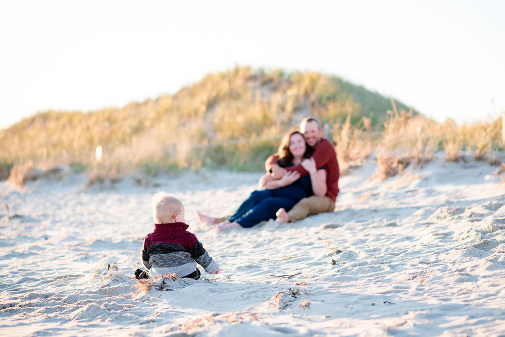 couple sitting on beach with their baby in focus in the foreground. On beach for engagement photos at lighthouse inn in West Dennis Cape cod, MA
