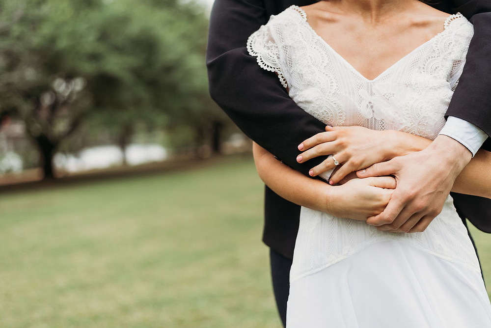 groom stands behind bride with his arms around hers. she is holding onto his hands. the photo is cropped so that you cannot see their faces. the attention is on the engagement ring. during their Austin elopement