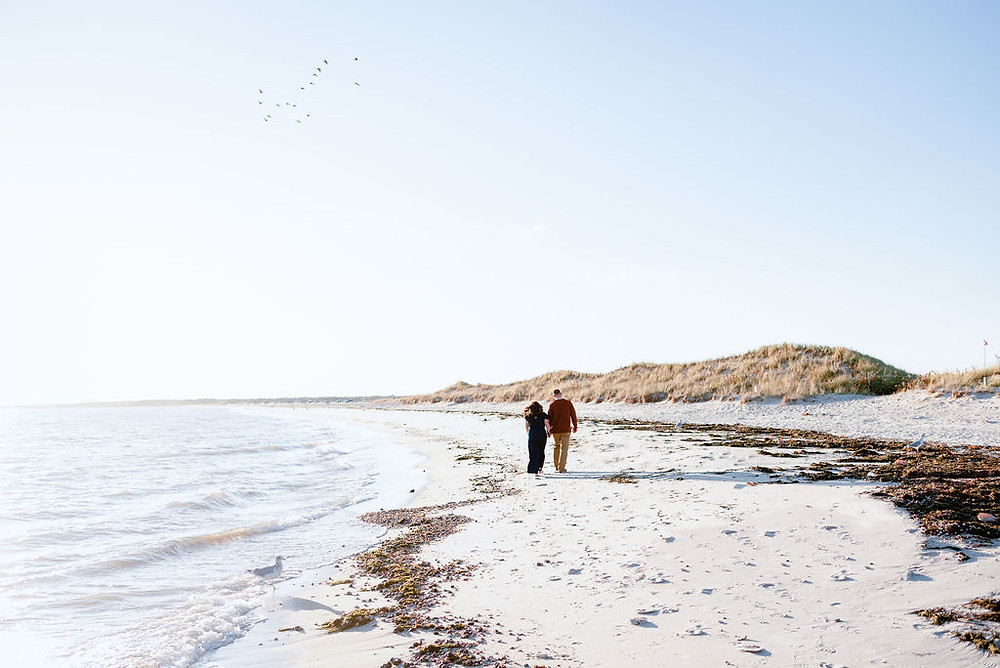 couple holding hands walking on beach for engagement photos at lighthouse inn in West Dennis Cape cod, MA