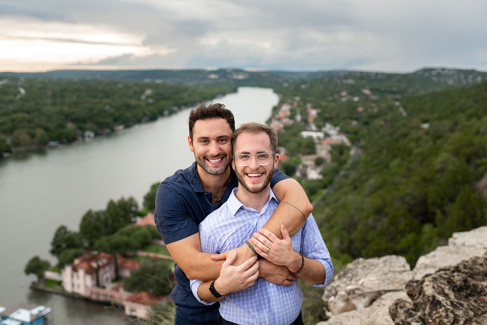 two guys smiling at the camera after getting engaged with the beautiful view of lake travis in the background from mount bonnell