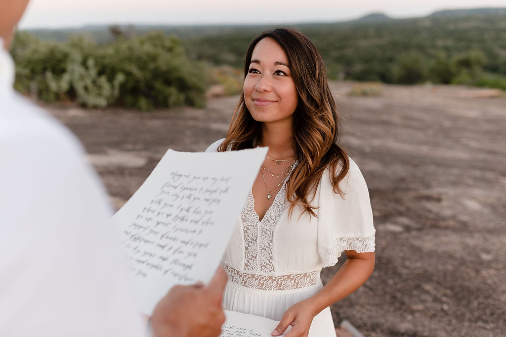 photo of the bride's face while she looks at the groom who is reciting his vows. you can see the vows in the foreground of the photo, in front of the bride, but they're not in focus