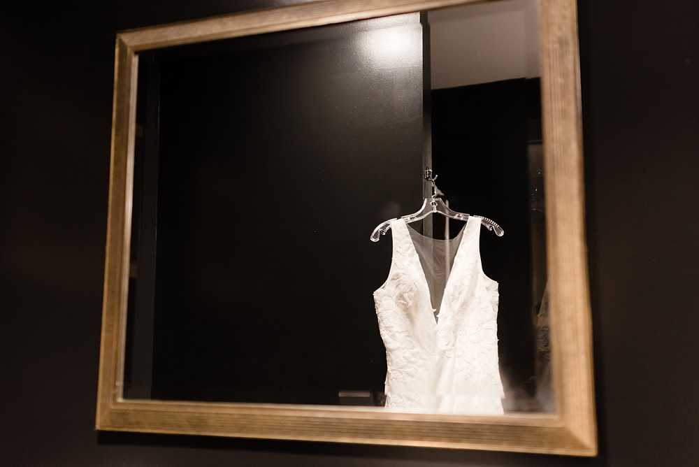 wedding dress reflection in mirror with black walls