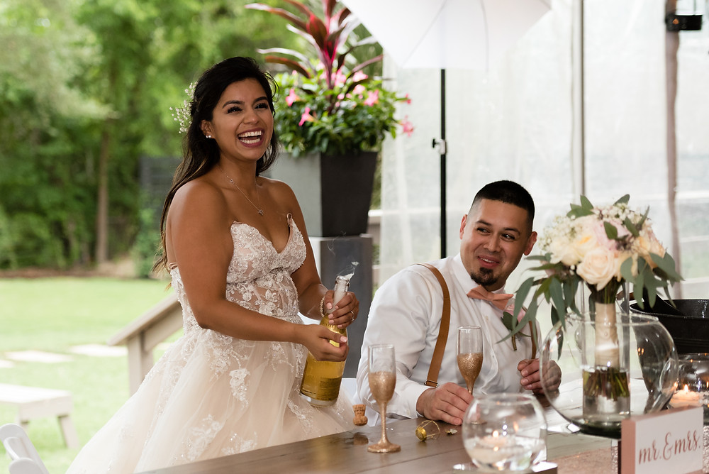 bride and groom popping champagne at wedding