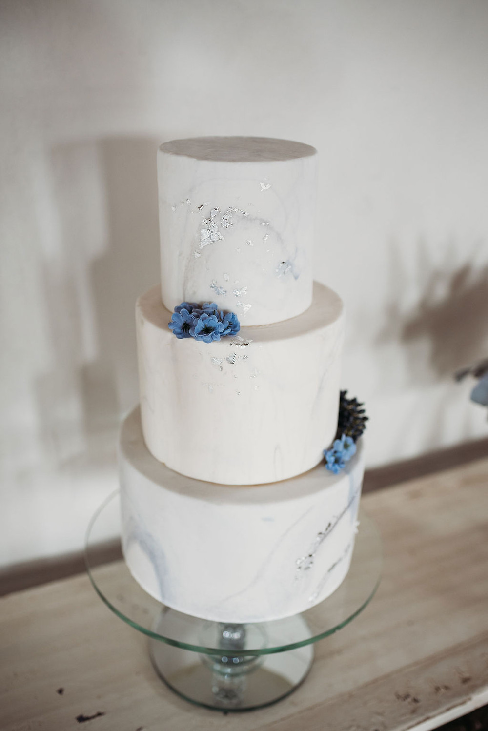 white marble wedding cake with silver foil and flowers