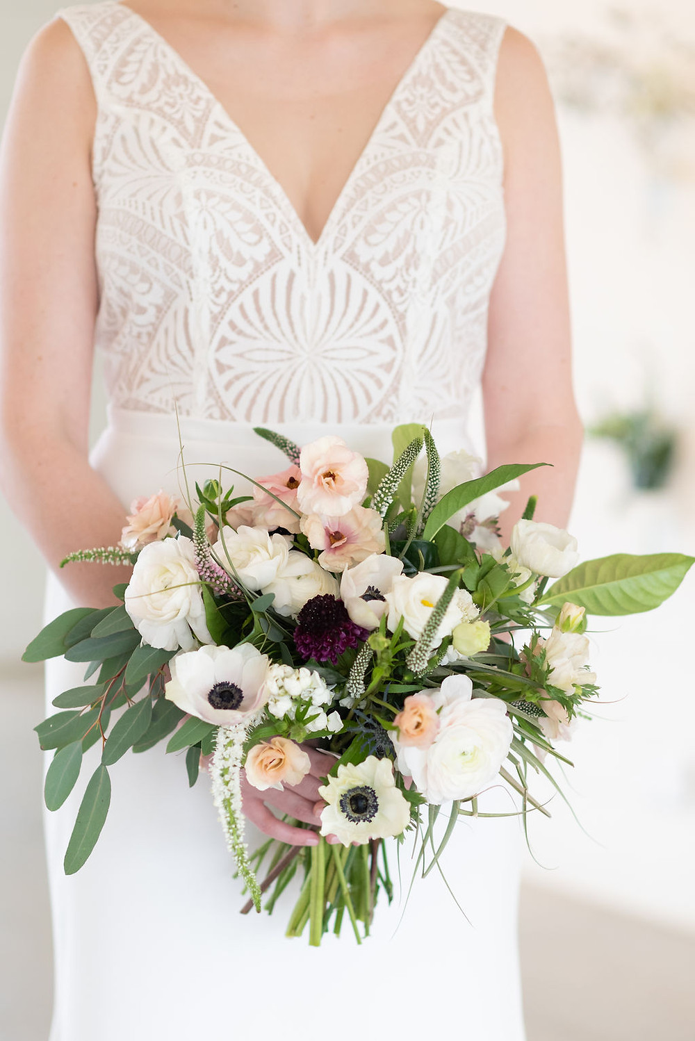 white and green bridal bouquet. bride is holding bouquet but the her head is not showing in the photo. it's from her shoulders to her knees