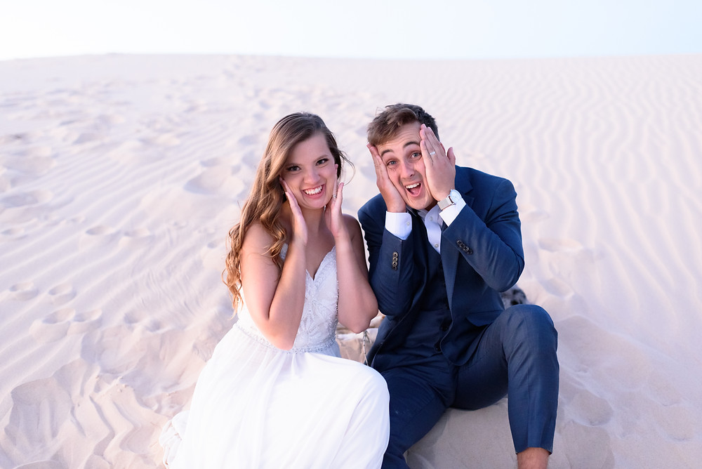 couple sits in sand next to each other making funny faces at the camera