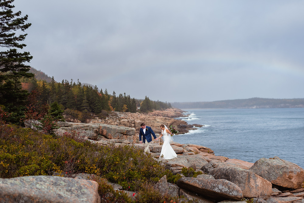 couple walking on rocks at gorham mountain trail at Acadia National Park during their Elopement