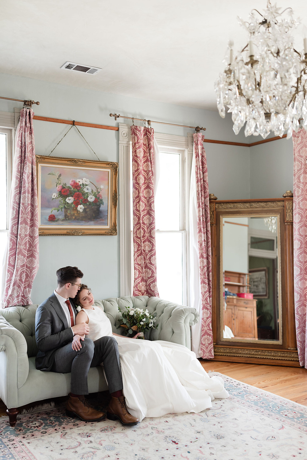 bride and groom sitting on a couch for their wedding photos. the couch is inside the bridal suite at the wedding venue barr mansion