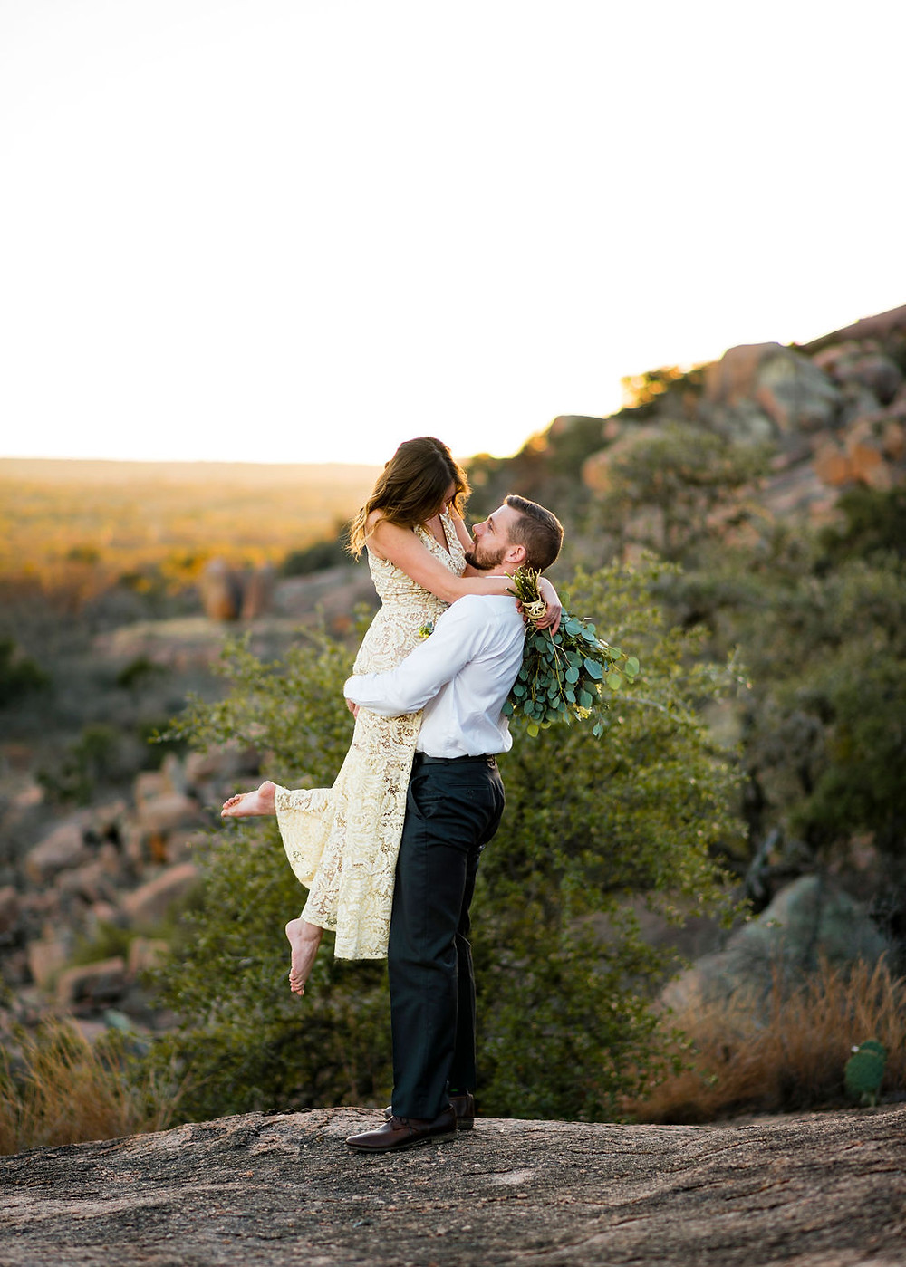 groom lifts up bride for wedding portrait. Bride has one bare foot kicked up into the air. Her arms are wrapped around his neck and she's holding her bouquet. In the background you can see the hill country. The couple is on enchanted rock for their elopement.